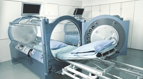 Nurse placed in front of a hyperbaric chamber.